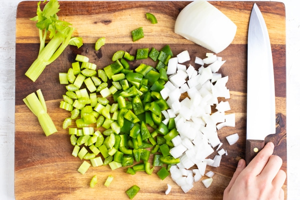 Diced celery, green bell pepper, and sweet onion as the holy trinity on a wooden cutting board.