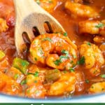 A wooden spoon scooping up a shrimp from a pot of Shrimp Creole.