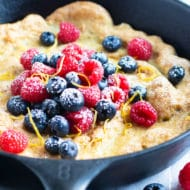 Dutch baby pancake recipe in a cast iron skillet with raspberries and blueberries.