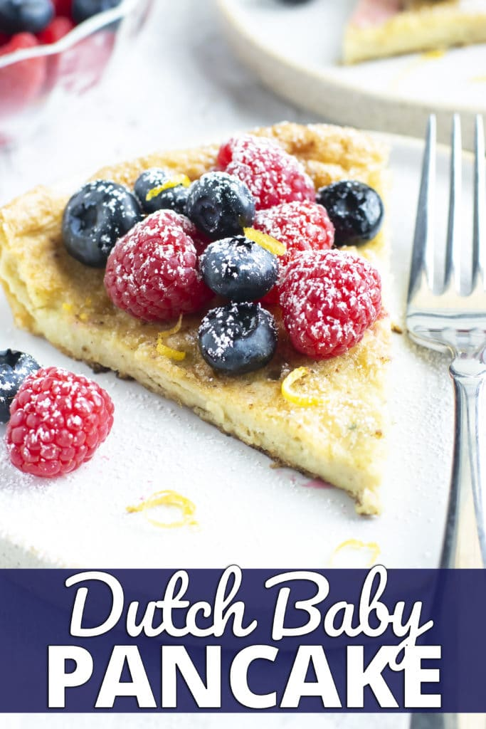 A serving of a Dutch Baby pancake with fresh berries, lemon zest, and powdered sugar on a white plate.
