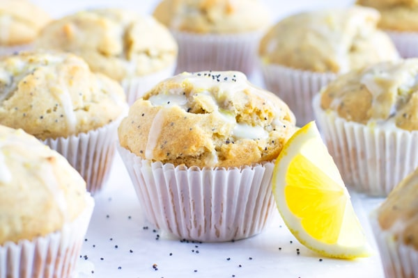 Lemon Poppy Seed Muffins with a lemon glaze on a white table.