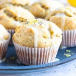 A tray full of healthy, gluten-free lemon muffins with a powdered sugar glaze and poppy seeds.