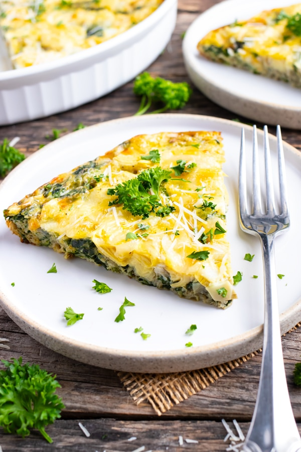 A white serving plate with a slice of spinach crustless quiche and a large baking dish full of it.