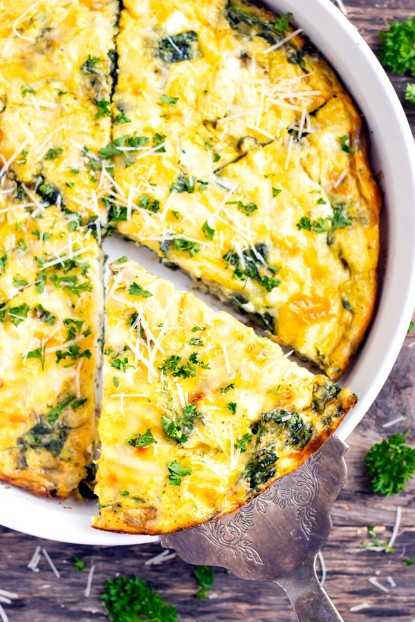 A slice of crustless quiche being picked up out of a baking dish.