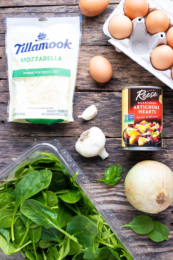 Large eggs, spinach, onion, garlic, artichoke hearts, and mozzarella cheese as the ingredients in a spinach crustless quiche egg bake recipe.