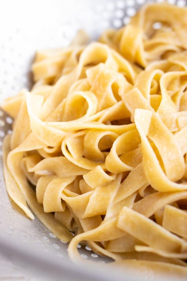 Vegan tagliatelle pasta in a colander.