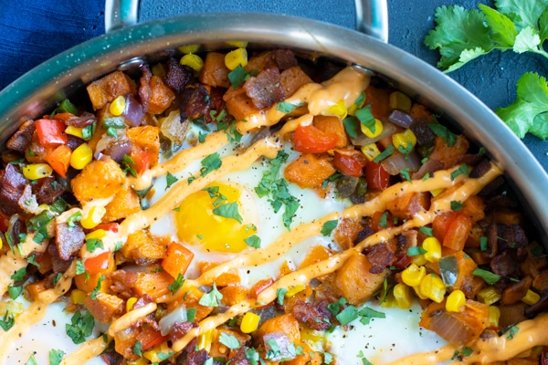 A stainless steel skillet full of sweet potato hash browns with eggs and sriracha mayo.