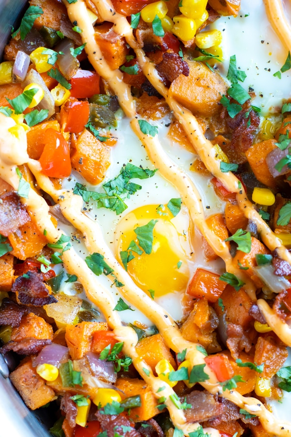 An egg in the middle of a sweet potato hash with sriracha mayo and cilantro on top.