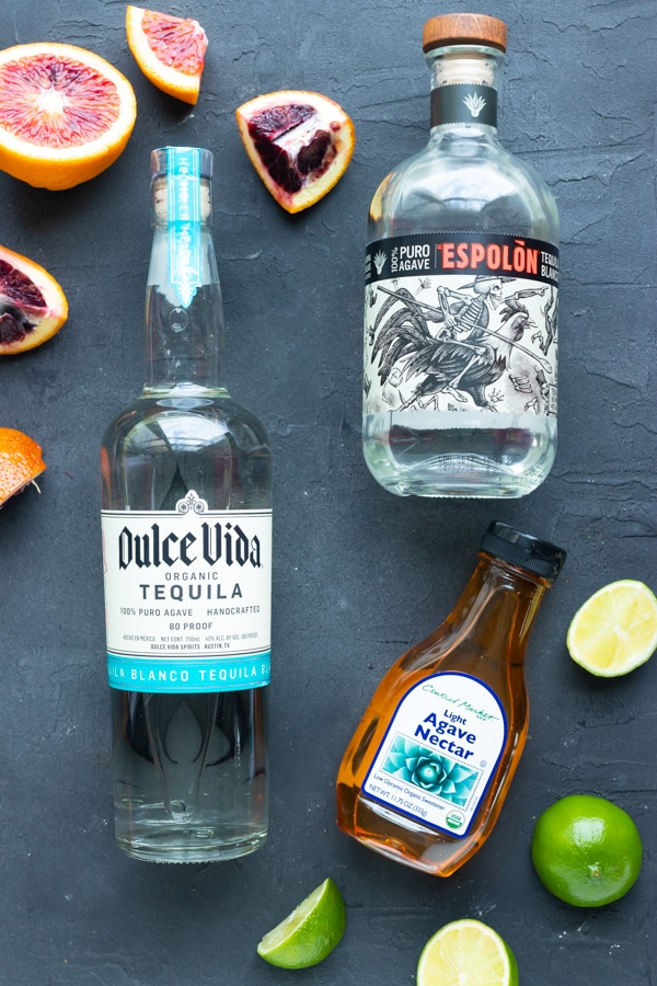 The best tequila for margaritas and other margarita ingredients on a black background.
