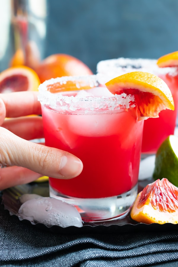 A hand holding a skinny margarita with blood orange juice.