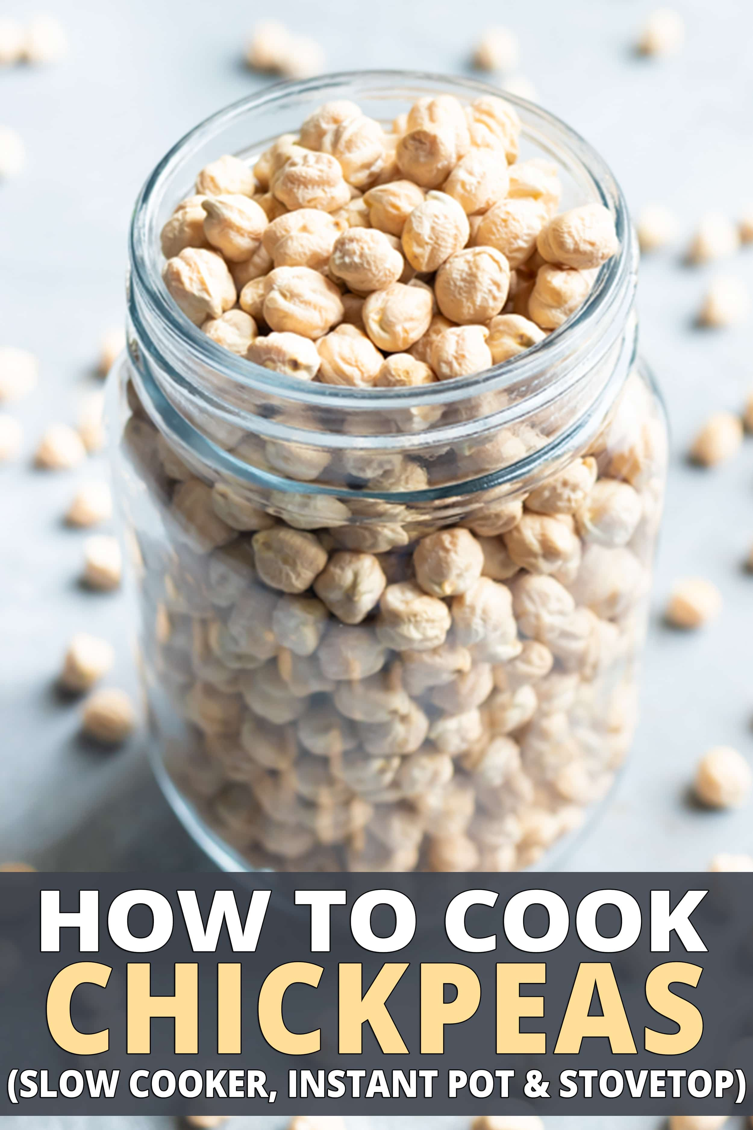 Dried chickpeas in a clear glass jar with a lot of chickpeas around it.