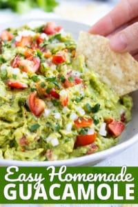 A tortilla chip being dipped into a healthy guacamole dip with tomatoes, onions, and cilantro.