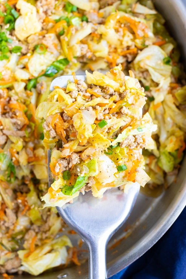 A skillet full of a ground turkey and cabbage recipe for egg roll in a bowl.