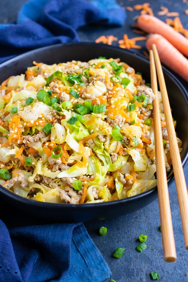 Keto and low-carb egg roll in a bowl recipe with chopsticks and a blue napkin.