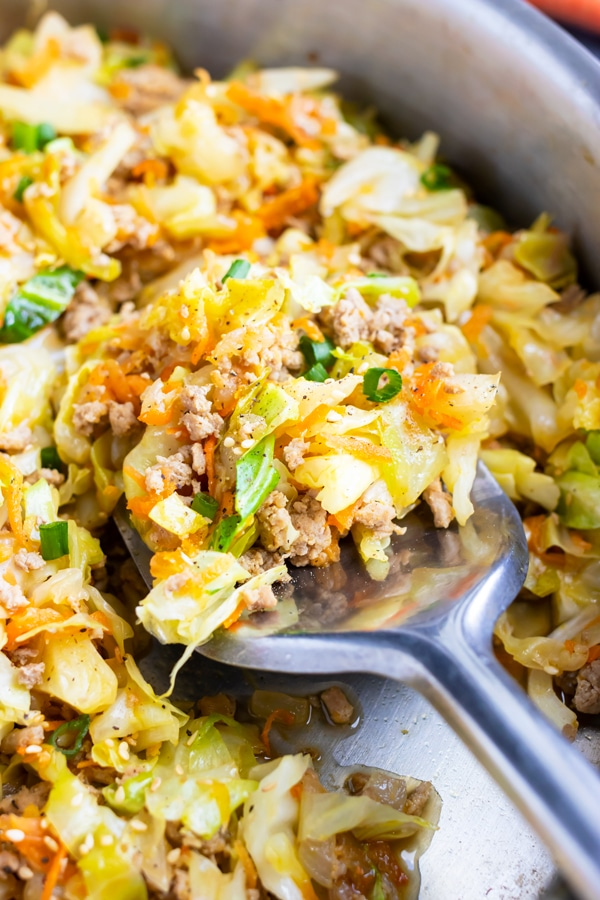 A metal spatula scooping up some shredded cabbage and ground turkey from a large skillet.