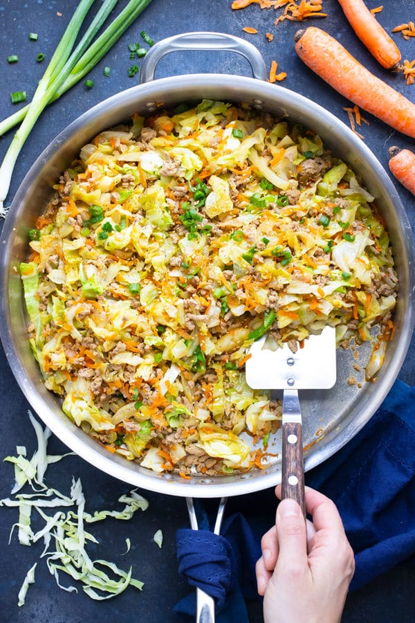 A large skillet full of a Paleo egg roll in a bowl recipe with cabbage, carrots, and ground turkey with a metal spatula scooping out a serving.