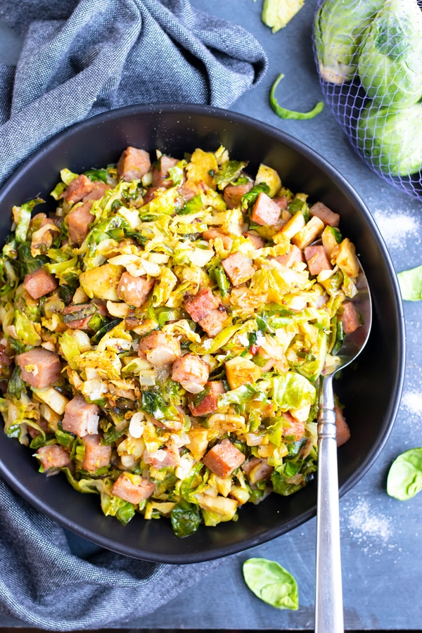 A large black serving bowl full of the best Brussels sprouts recipe that have been sautéed in a skillet with leftover ham.