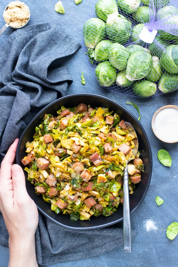 A bag full of Brussels sprouts next to a serving bowl full of sauteed and shredded Brussels sprouts with cubed ham.