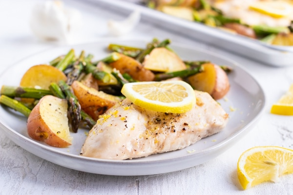 A white plate full of healthy lemon chicken with roasted potatoes and asparagus.
