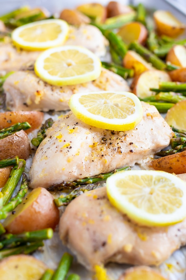 Baked chicken breasts with lemon slices on top surrounded by red potatoes and asparagus.