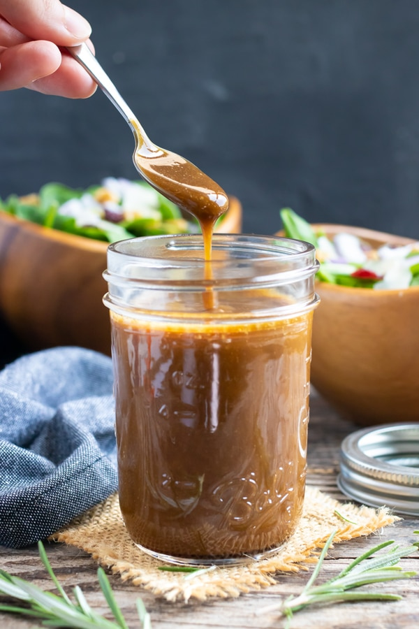 A mason jar full of balsamic and maple syrup salad dressing with two salads in the background.