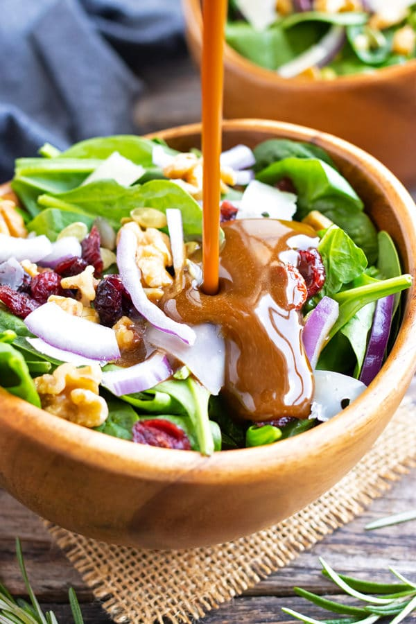 A healthy and easy balsamic vinaigrette dressing being poured onto a spinach salad with cranberries.