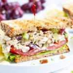 Chicken salad sandwich with grapes, tomatoes, and lettuce and served with potato chips.