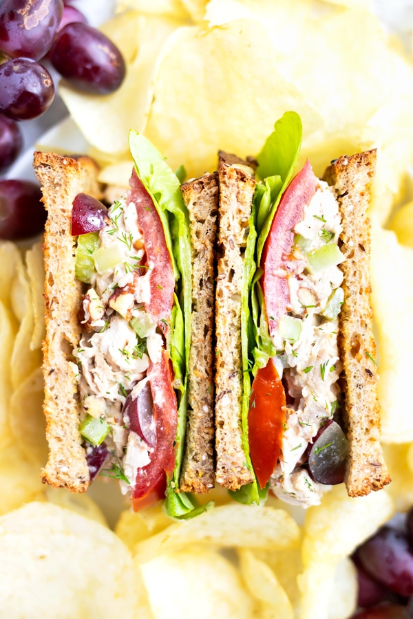 Two halves of a chicken salad sandwich surrounded by potato chips and red seedless grapes.