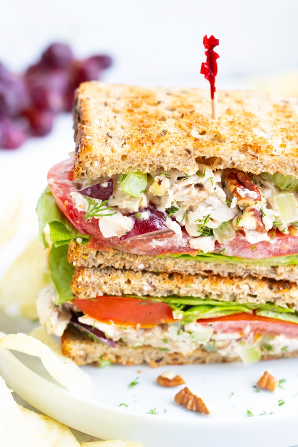 Chicken salad sandwich with a toothpick in it on a white plate with grapes in the background.