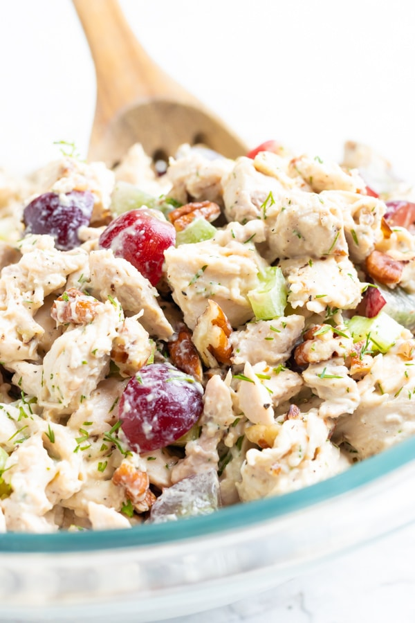 Healthy chicken salad with grapes in a clear glass bowl with a wooden spoon.