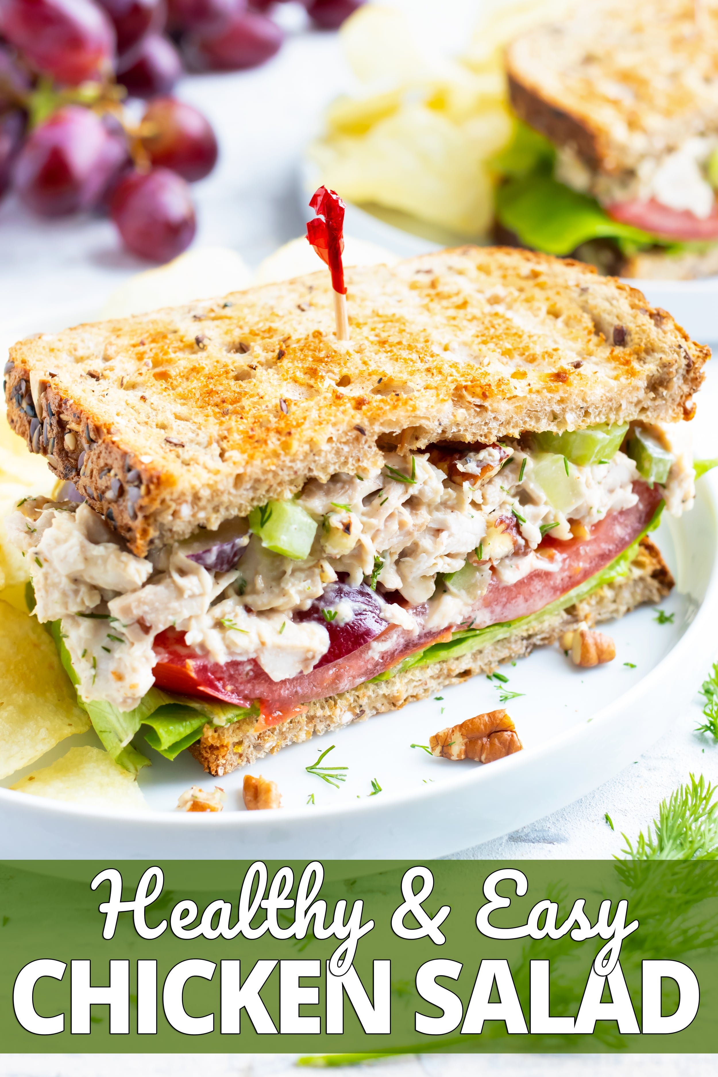 Chicken salad sandwich with a red toothpick on a white plate with potato chips.