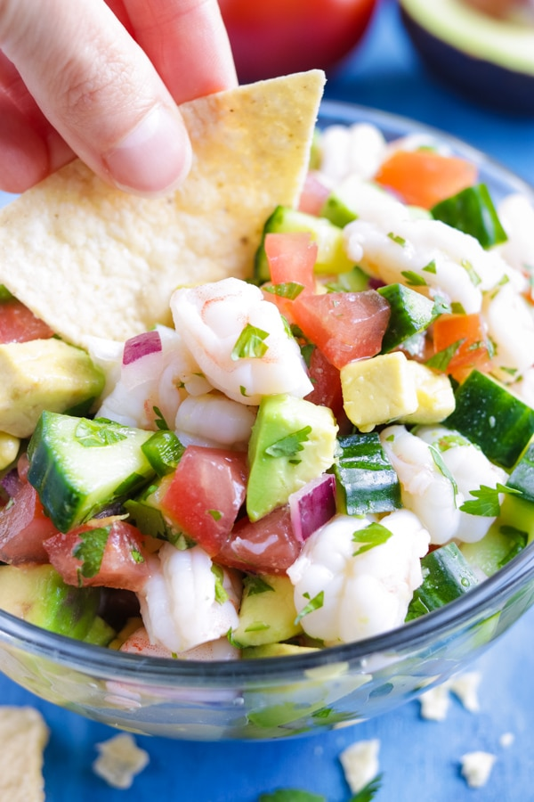 Low-Carb, healthy, and easy Mexican Shrimp Ceviche with a hand dipping a chip into it.
