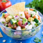 A clear bowl full of an easy shrimp ceviche recipe with a tortilla chip in it.