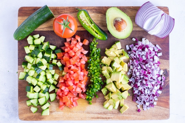 A wooden cutting board with diced cucumber, tomatoes, jalapeno, avocado, and red onion.
