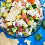 An appetizer bowl full of a shrimp and avocado Mexican dip recipe surrounded by tortilla chips.
