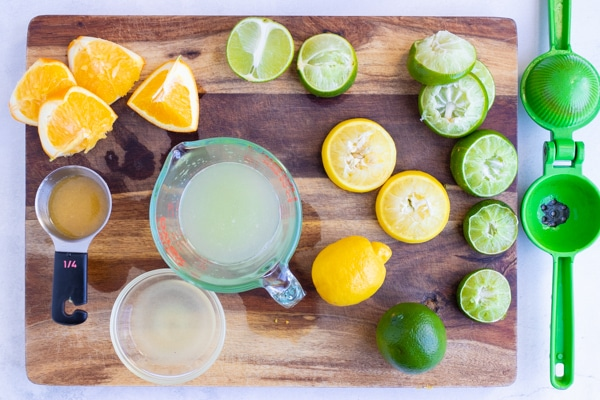 Limes, lemons, and oranges being juiced on a wooden cutting board.