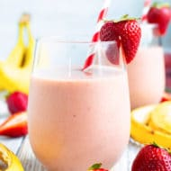 Two glasses full of a strawberry banana smoothie recipe with a red and white striped straw.