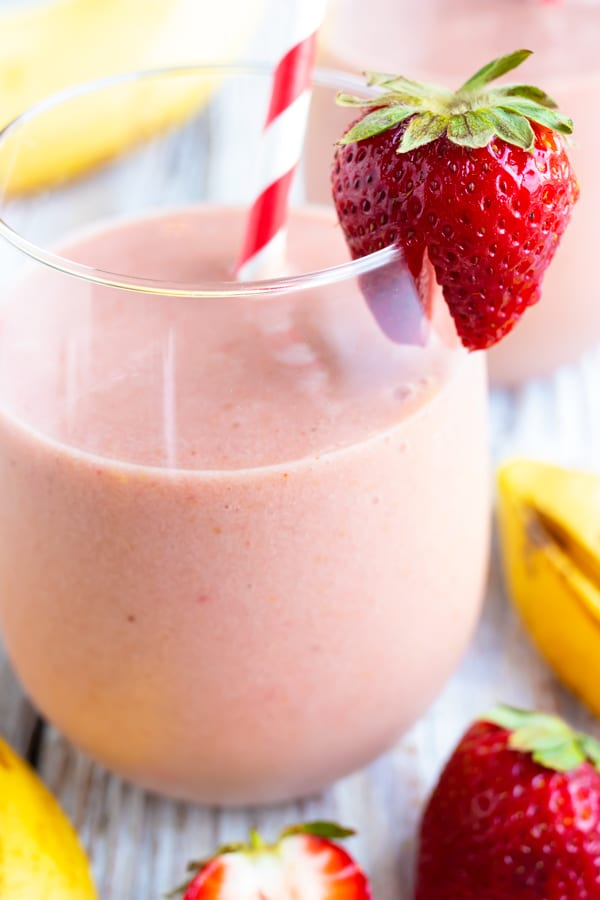 A close-up of a strawberry on a glass full of a strawberry smoothie recipe.