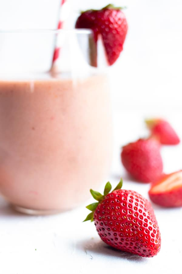 Fresh strawberries lying next to a glass full of a smoothie recipe.