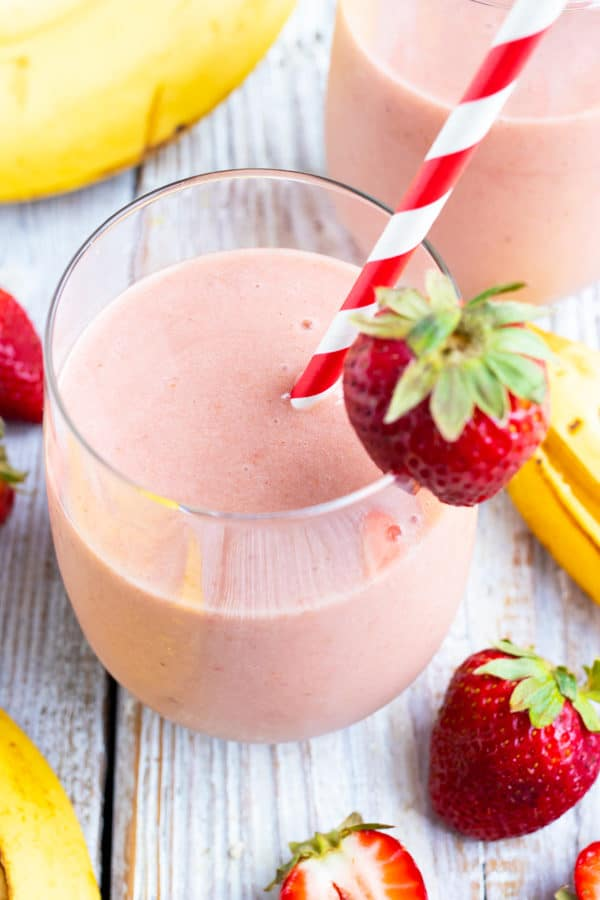 A glass full of a strawberry and banana smoothie with a strawberry as a garnish and a red/white striped straw.