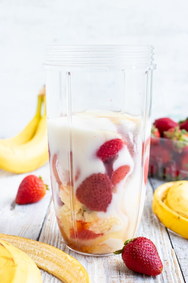 Frozen strawberries, bananas, honey, milk, and yogurt in a clear blender container.
