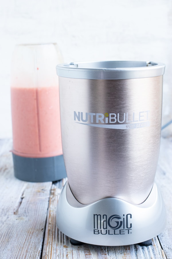 A Nutribullet, or high speed blender, with a strawberry smoothie in the background.