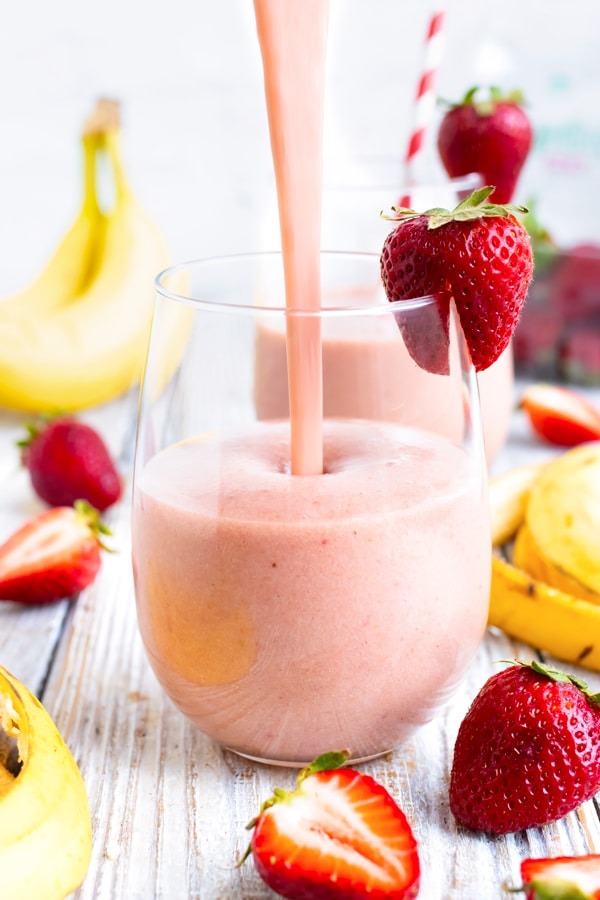 Strawberry banana smoothie being poured into a glass with strawberries and bananas around it.
