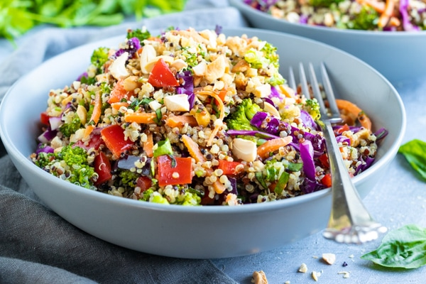 Thai peanut quinoa salad recipe in two grey bowls with cilantro in the background.