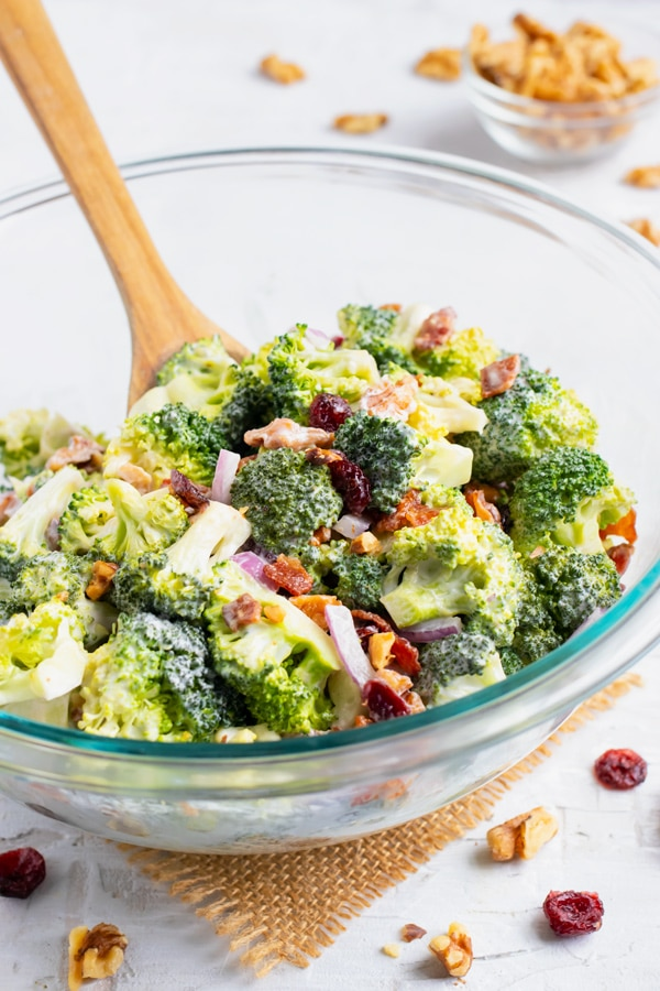 Broccoli Salad in a clear glass bowl with a wooden spoon stirring it.
