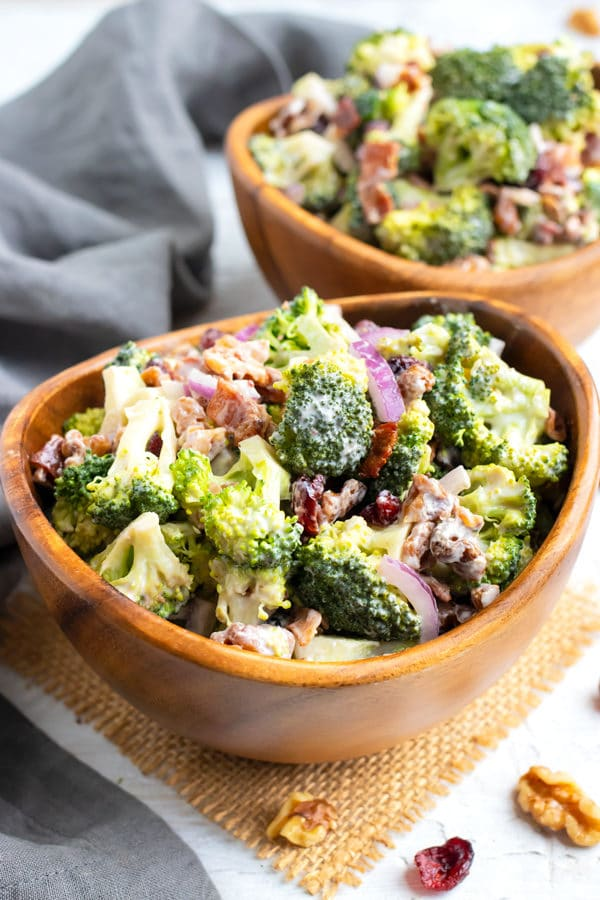 A wooden serving bowl full of a cold broccoli salad recipe with walnuts, cranberries, and bacon.
