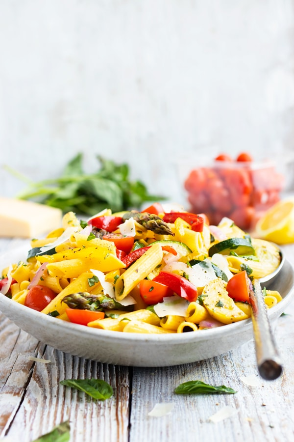 A serving bowl full of a pasta primavera recipe with a silver spoon.