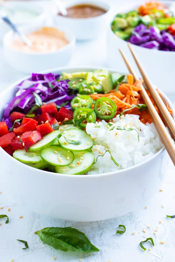 Vegan sushi bowls made with perfect sushi rice, cucumbers, bell peppers, avocado, carrots, and cabbage.