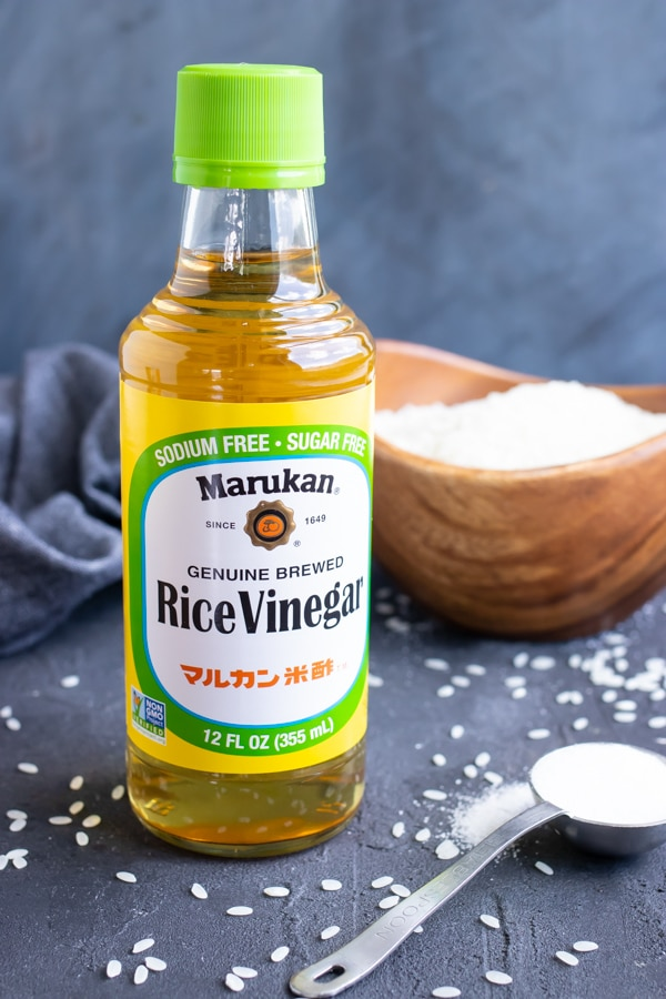 A bottle of rice vinegar and sugar as ingredients to season sushi rice.