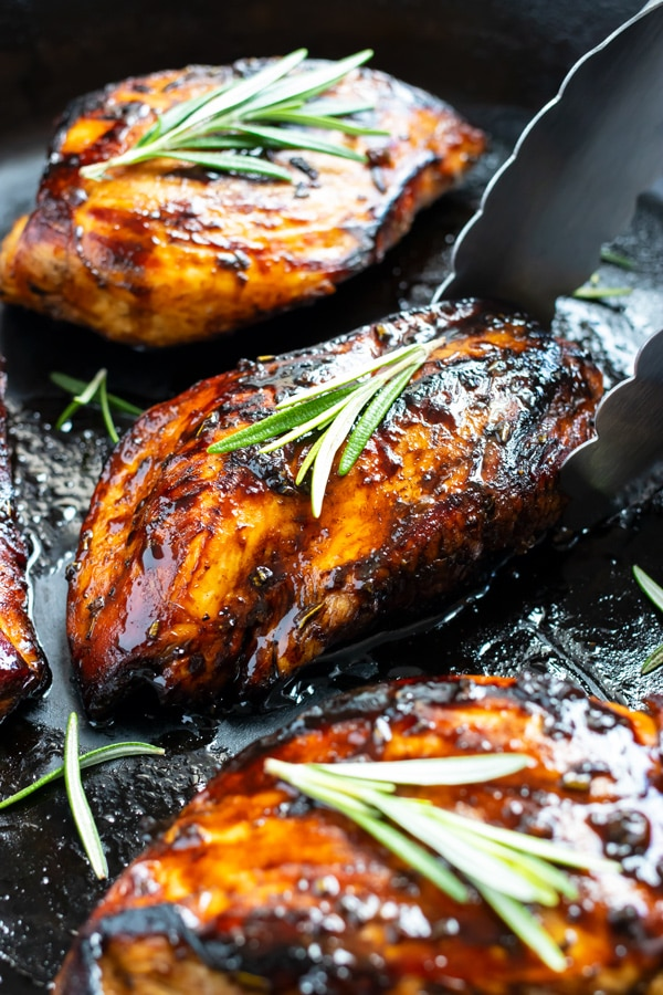 A cast-iron skillet with balsamic glazed chicken being cooked in it and picked up with tongs.